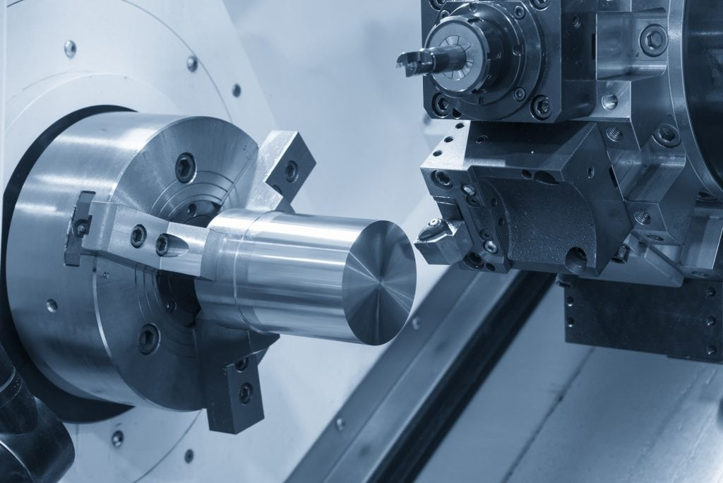 Close up of a CNC lathe clamping a raw material steel rod