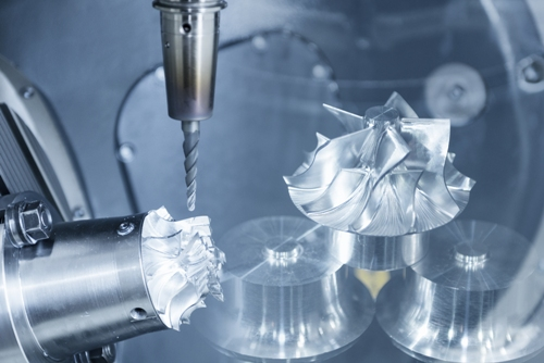 A five-axis CNC machine cutting an aerospace turbine part